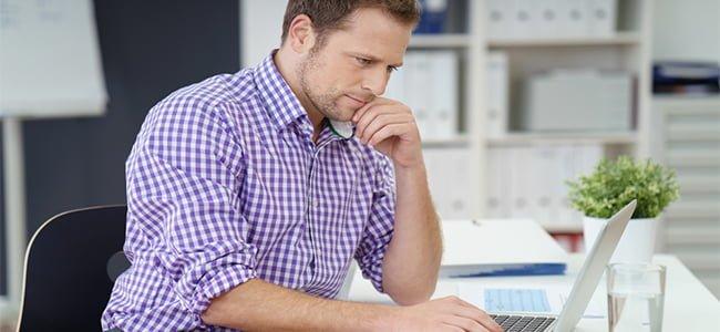 man wearing purple check shirt at work